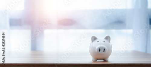 Fotografía white piggy Bank on a window light background with copyspace for design
