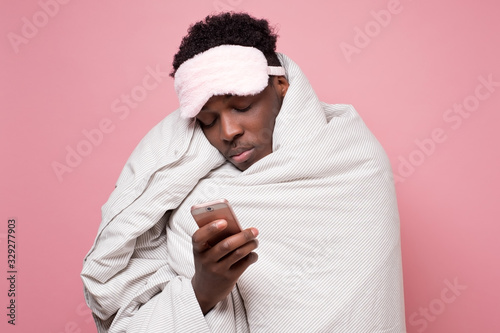 Photo Tired young black man is awaked by the phone conversation at night