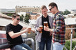 Happy smiling male friends drinking beer and clinking glasses at bar or pub on rooftop, copy space. Friendship and celebration concept