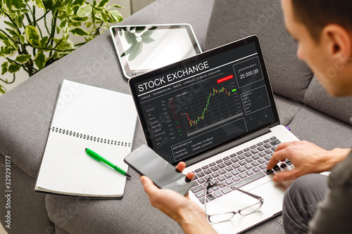 Photo Conceptual hand writing on a laptop with graphs of the financial crisis