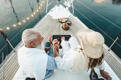Fototapeta Senior couple celebrating wedding anniversary on sailboat - Happy mature people having fun on boat trip vacation - Love relationship and travel elderly people lifestyle concept obraz