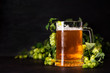 canvas print picture - Mug of beer with hop cones on dark wooden background. October fest background