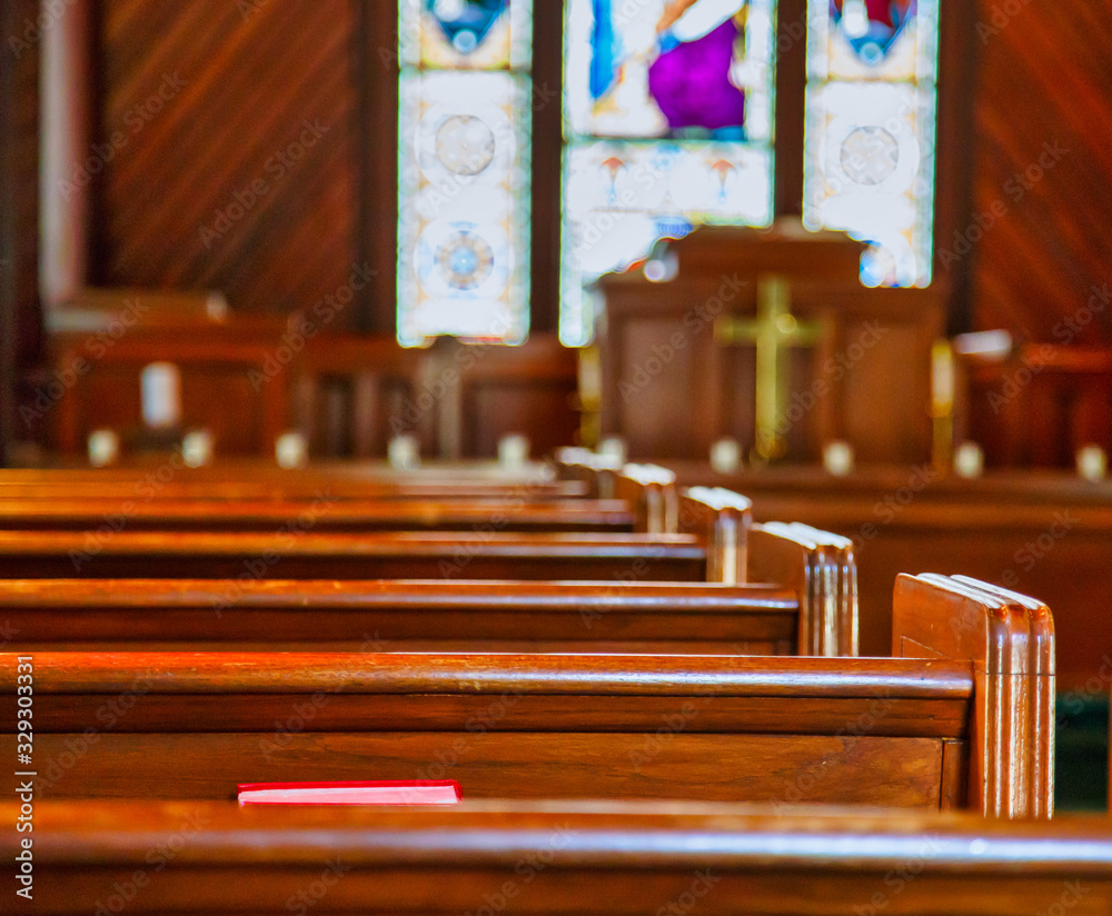 Fototapeta Stained glass windows in small church with wood pews