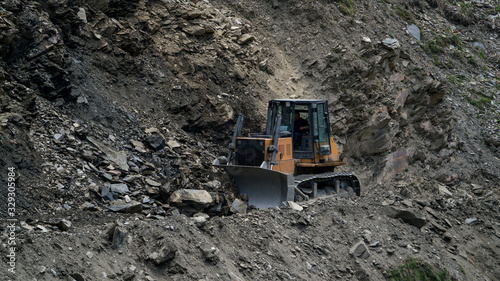 Fototapeta Tractor clearing the road from rockfall summer