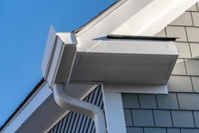 Gutter System That Collects Water Shedding Off The Roof, With Slip Connector, End Cap, Elbow Tube, Gutter Hanger, Gutter Drop Connecting  Outlet To The Downspout, Soffit, Fascia, Gray Shingle Siding