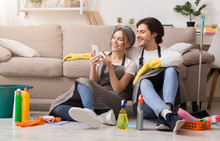 Smiling Young Couple Relaxing With Smartphone After Cleaning Apartment