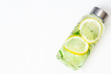 Lemonade with fresh lemon. Lemon and lime water and ice in a glass bottle. White background. Copy space. Concept: healthy life, diet, sport, detox. Drink.