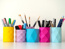 Colored Pencil And Pens Holders Decorating A White Table