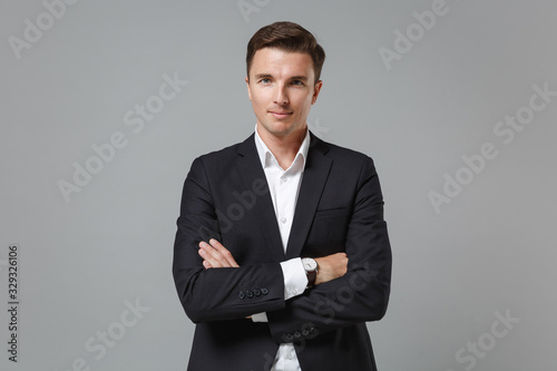 Fototapeta Smiling young business man in classic black suit shirt posing isolated on grey wall background studio portrait. Achievement career wealth business concept. Mock up copy space. Holding hands crossed. obraz