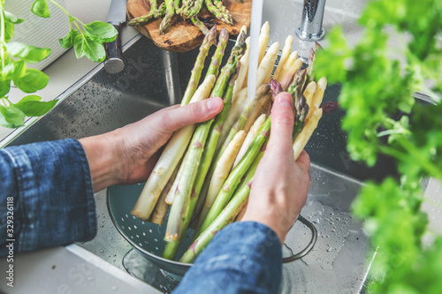 cropped shot of male hands in soil washing fresh asparagus in kitchen sink Canvas Print