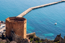 The Historical Ruins Of Red Tower And Castle Walls Next To Harbour Of City Alanya In Antalya Province.