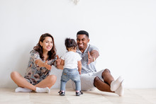 Beautiful Young Caucasian Woman Couple And An African American Man Are Pulling Their Hands To Their Charming Mixed Race Daughter. Concept Of Posing On White Background. Copyspace