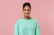 Smiling young african american woman girl in green sweatshirt posing isolated on pastel pink background studio portrait. People sincere emotions lifestyle concept. Mock up copy space. Looking camera.