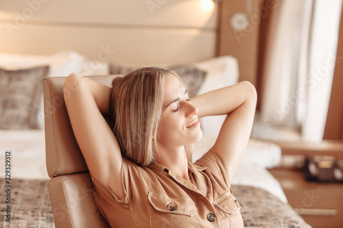 Photo Charming tired young beautiful woman is resting in a comfortable chair after long flight in luxury hotel room