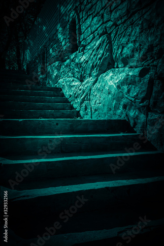 Darkness and horror, ghost house. Dark stone ruined old staircase from the basement with mystical shadows and strange light