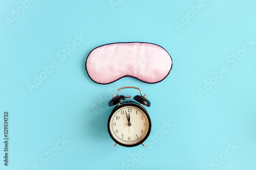 Fototapeta Pink sleep mask for eyes and black alarm clock on blue background. It 's midnight Top view Copy space. Concept eye protection from light for good sleep and melatonin production obraz