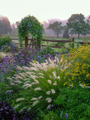 Naklejka Na szybę Vertical image of a beautiful country garden in fall with flowers, herbs, shrubs, trees, ornamental grasses, an arbor (arch) covered with 'Heavenly Blue' morning glory, and a fence and gate