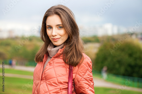 Close up portrait of a young beautiful brunette girl in coral coat Tablou Canvas