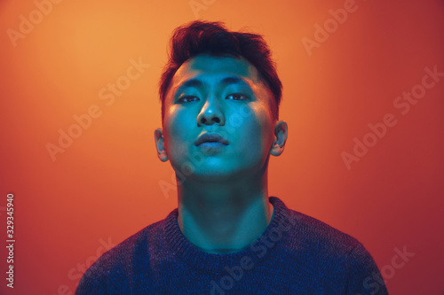 Canvastavla Portrait of a guy with colorful neon light on gradient studio background