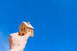 家の模型を青空にかかげる。住宅購入コンセプト。