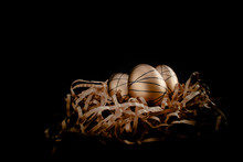 Easter Goldenand White Decorated Eggs In Nest On Black Background . Minimal Easter Concept Copy Space For Text. Top Horizontal View