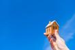 家の模型のおもちゃを青空にかかげる手。マイホームを買うイメージ。