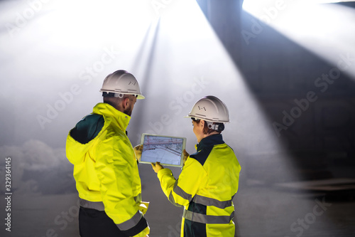 Fotografie, Obraz Rear view of engineers standing on construction site, holding tablet