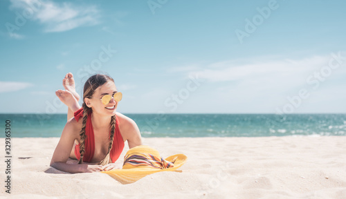 Obraz Woman enjoying her vacation by the sea tanning in the beach sand - fototapety do salonu