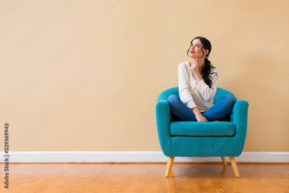 Fototapeta Young woman in a thoughtful pose sitting in a chair