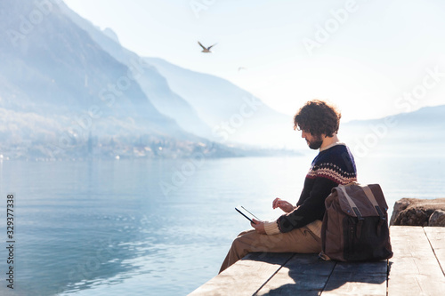 Fototapeta Freelancer workplace at sea beach. Young man working in traveling from outdoor office at nature. Traveler using tablet and the Internet and sitting on pier. Successful freelance. Copy space. obraz