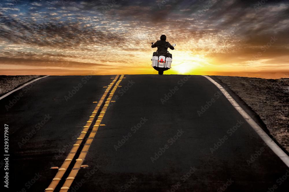 Fototapeta Motorcycle rider on street riding toward sunset sky