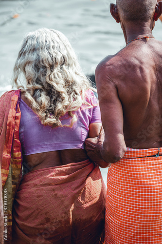 Fotografering Old indian man helping elderly indian woman with long grey hair to enter the waterr of the holy river Ganges for purification religious ritual