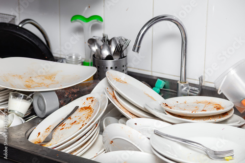 Fotografija Metal sink full of dirty dishes, crockery, tableware