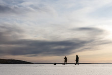 Two Men And A Dog In The Distance On The Snowy Ground Amid The Winter Sunny Sky