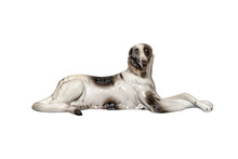 Porcelain Figurine In The Shape Of A Dog Lying On The Ground With Folded Paws, Isolated On A White Background With A Clipping Path.