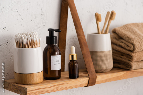 Cuadros en Lienzo Selective focus of hygiene and cosmetic products with towels on shelf in bathroo
