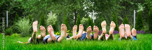 Photo Family relaxing on green grass, barefoot laying down and looking into the sky