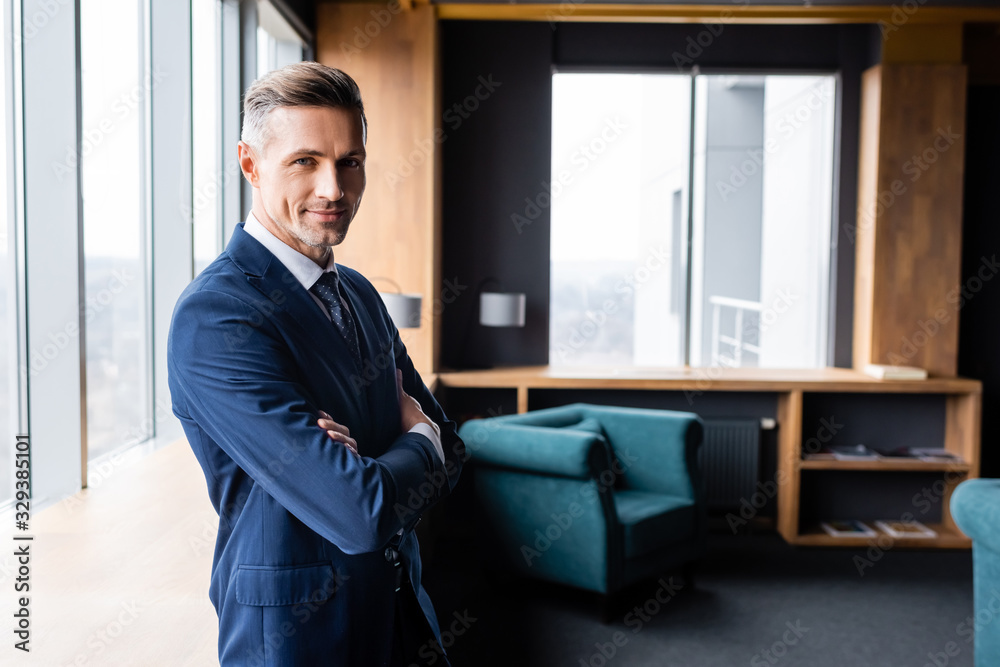 Fototapeta smiling businessman in suit with crossed arms looking at camera in hotel