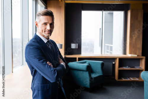 smiling businessman in suit with crossed arms looking at camera in hotel Fototapeta