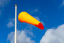 An Orange Windsock Flying In The Breeze On A Flag Pole With A Blue Sky Behind
