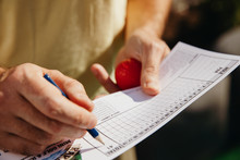 Midsection Of Player Filling Score Card At Golf Course