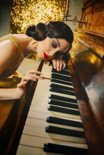 Closeup Retro Portrait Young Beautiful Great Gatsby Woman Finger Wave Hairstyle Smokey Cat Eyes Makeup Red Lips. Musician Plays The Piano Melody Touches Keys Her Hand Gold Dress Fashion Old Style 1920