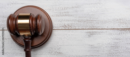 Fototapeta Gavel and pedestal on a white wood background with copy space