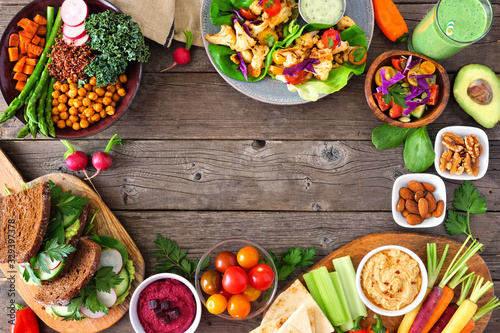Healthy lunch food frame. Table scene with nutritious Buddha bowl, lettuce wraps, sandwiches, salad and vegetables. Overhead view over a rustic wood background. Copy space.