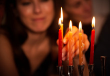 Close-up Of Woman Holding Lit Candle On Menorah During Hanukkah