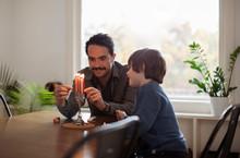 Boy Looking At Smiling Father Burning Candles On Menorah During Hanukkah Festival