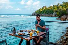 Men Having Breakfast Ocean Fro...