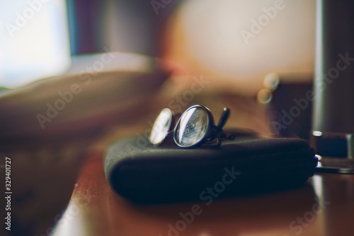 reading glasses on the bedside table with artistic bokeh lights, fine art vintage and pictorial blur Canvas Print