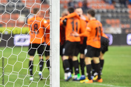 Detail of goal's post with net and joy of football team in the background Fototapet