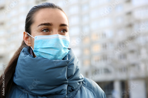 Obraz Woman wearing disposable mask outdoors. Dangerous virus - fototapety do salonu